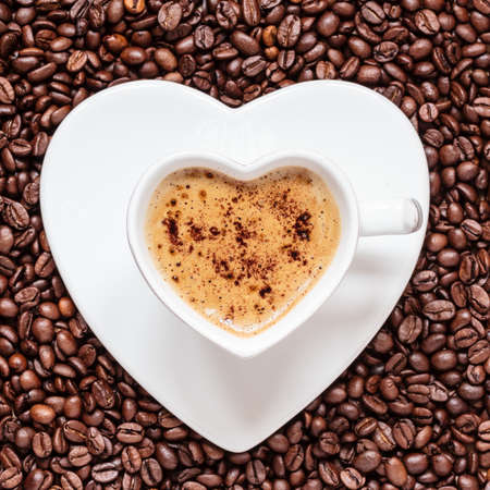 Hot beverage. White coffee cup heart shaped with cappucino latte on roasted beans background photo