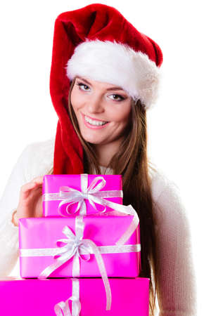 Christmas winter happiness concept. Woman in wearing santa helper hat holding stack of pink presents gift boxes isolated on white photo