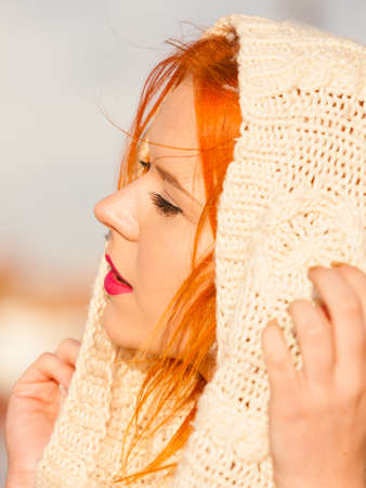 Winter fashion. Beauty face portrait redhaired young woman in warm clothing outdoor enjoying sunlight on sunny day. photo