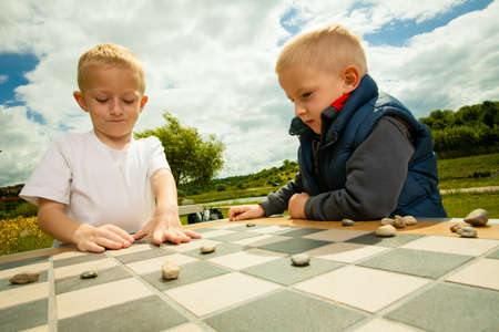 sibling rivalry: Draughts board game. Little boys clever children  kids playing checkers thinking, outdoor in the park. Childhood and development