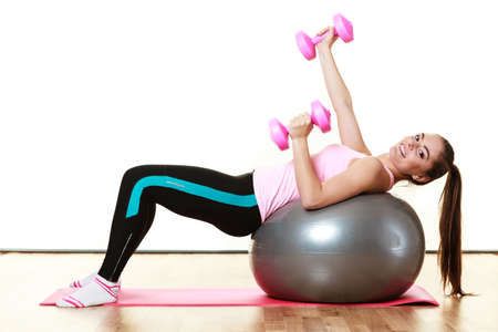 dumb bells: Healthy active lifestyle. Woman with gym ball and dumb bells doing exercise, lifting hand weights isolated on white