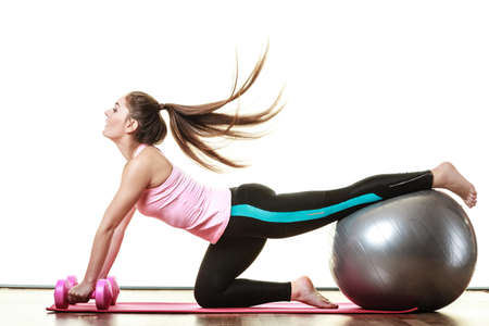 dumb bells: Healthy active lifestyle. Woman with gym ball and dumb bells doing exercise, isolated on white