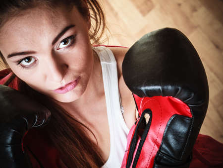 martial arts woman: Martial arts or self defence concept. Sport boxer woman in black gloves. Fitness girl training kick boxing. Stock Photo