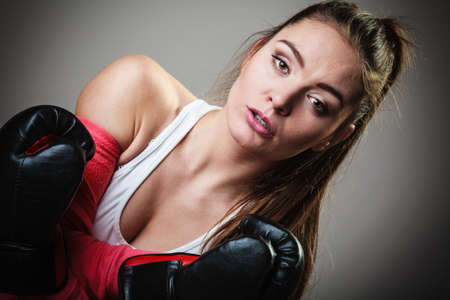 girl kick: Martial arts or self defence concept. Sport boxer woman in black gloves. Fitness girl training kick boxing. Stock Photo