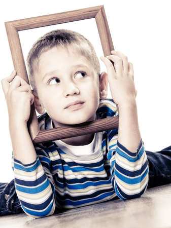 looking in corner: Portrait of little funny blonde boy child holding photo frame framing his face looking into the corner studio shot