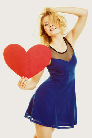 Red heart card. Love symbol. Beautiful woman holding valentine day symbol. Cute crazy blonde girl in blue dress expressing tender feelings.
