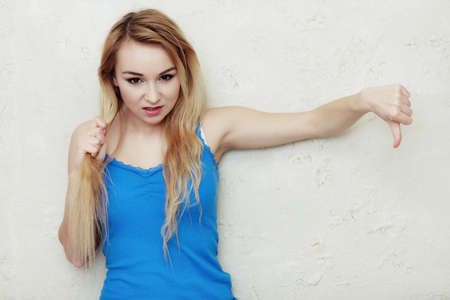 hair problem: Hair problem. Blond woman teenage girl holding her damaged dry hair showing thumb down hand sign gesture. Indoor.