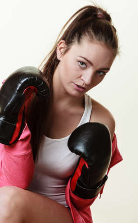 Martial arts or self defence concept. Sport boxer woman in\ black gloves. Fitness girl training kick boxing.
