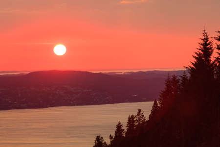 Panoramic view from hill of Bergen and fjord landscape red sky sunset scenery, Norway photo