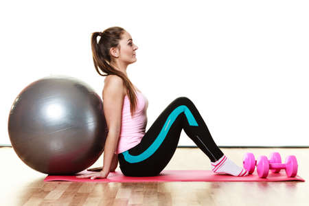 dumb: Woman with gym ball and dumb bells sitting on exercise mat, isolated on white background Stock Photo