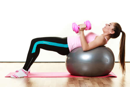 dumb bells: Healthy active lifestyle. Woman with gym ball and dumb bells doing exercise, lifting hand weights isolated on white background