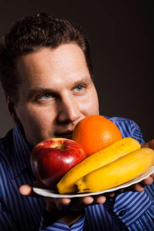 Diet and nutrition. Happy young man smelling fruits on dark gray. Guy recommending healthy nutrition. photo