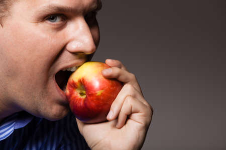 recommending: Diet and nutrition. Happy young man eating biting apple seasonal fruit on dark gray. Guy recommending healthy nutrition or dental care.