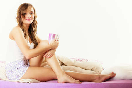 Relax, home, happiness and people concept. Young woman sleepy girl sitting relaxing on bed at morning with cup of tea coffee Stock Photo - 34697591