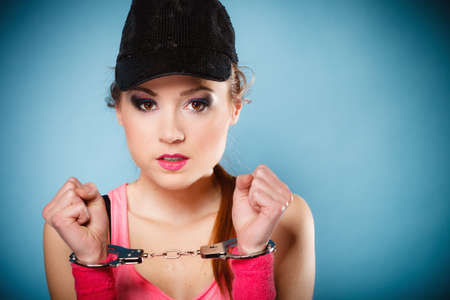 juvenile delinquent: Teen crime, arrest and jail - Criminal teenager girl prisoner woman in handcuffs blue background