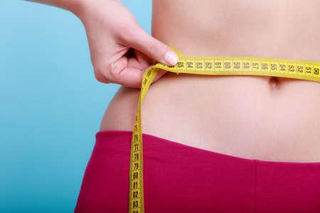 Čas pro dieta hubnutí hubnutí. Péče o zdraví a zdravá výživa. Mladí fitness žena fit dívka s páskou opatření měření její pas na modrozelené