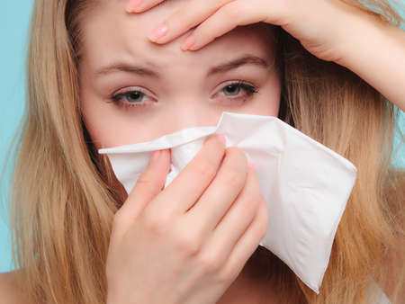 symptom: Flu cold or allergy symptom. Sick woman girl with fever sneezing in tissue on blue. Health care.