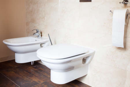 physiological: Hygiene and physiological needs. Closeup of white porcelain bidet and toilet wc. Interior of bathroom.