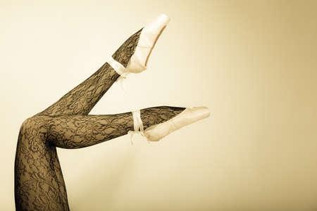 zapatillas ballet: hermosa bailarina de ballet de la mujer, que forma parte de las piernas del cuerpo en zapatos y medias de encaje negro dispararon estudio tono vintage años Foto de archivo