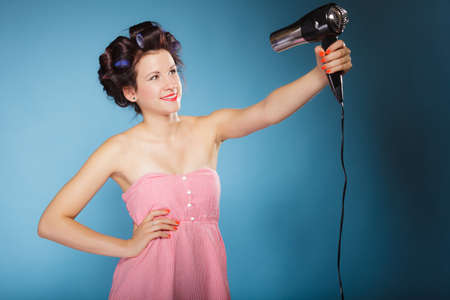 Young woman preparing to party having fun, funny girl styling hair with hairdreyer retro style on blue