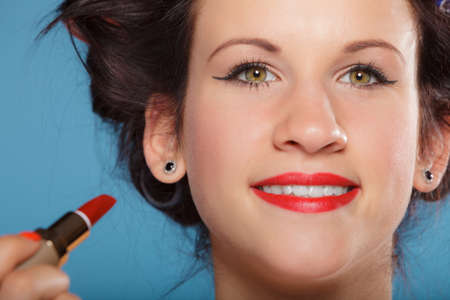 makeover: Cosmetic beauty procedures and makeover concept. Closeup part of woman face applying red lipstick on blue Stock Photo