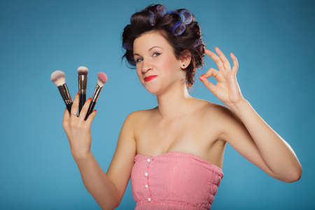 Cosmetic beauty procedures and makeover concept. Woman in hair rollers holding makeup brushes set making ok sign gesture on blue photo