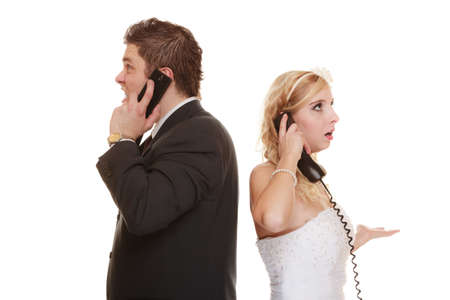 fury: Wedding relationship difficulties. Angry woman and fury man talking on phone. Couple bride groom quarrelling screaming isolated on white. Stock Photo