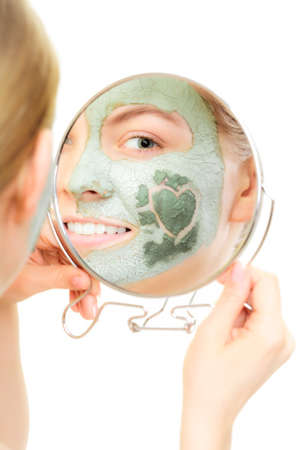 complexion: Skin care. Woman in clay mud mask on face with heart on cheek looking in the mirror isolated on white. Girl taking care of dry complexion. Beauty treatment.