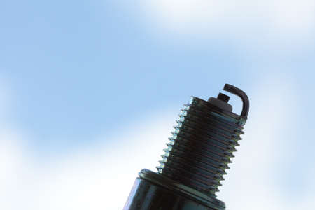 fuel chamber: Auto service. New car spark plug as spare part of auto transportation on blue sky background.