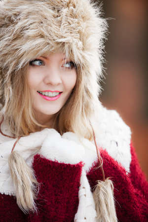 Winter fashion. Closeup smiling young woman wearing fashionable wintertime clothes fur cap outdoor portrait photo