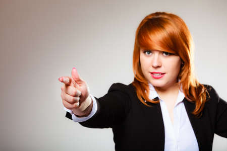 Business woman point finger at you looking at camera on gray background photo
