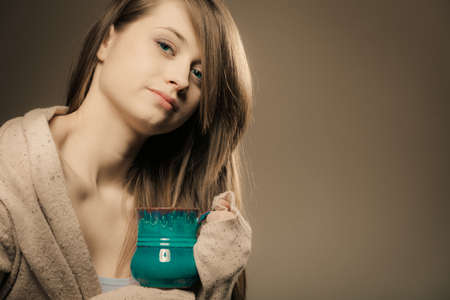 Hot beverage. Sleepy girl holding cup mug of drink tea or coffee. Woman in warm sweater warming herself photo