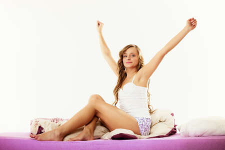 tenager: Healthy lifestyle. Cheerful happy woman teen girl waking up with a smile in bed and stretching her arms up