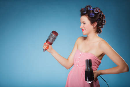 blow drier: Young woman preparing to party having fun, funny girl styling hair with curlers hairbrush and hairdreyer retro style blue background Stock Photo
