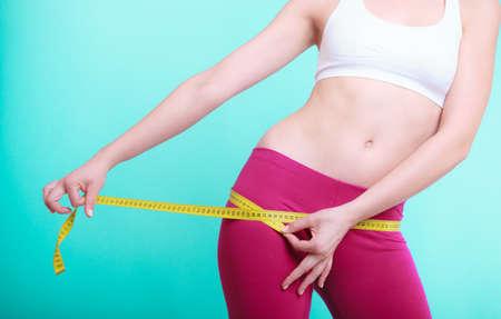cinta metrica: Tiempo para la p�rdida de peso dieta de adelgazamiento. Atenci�n de la salud y la nutrici�n saludable. Fitness mujer ni�a apta de los j�venes con cinta m�trica que mide sus lomos en la turquesa Foto de archivo