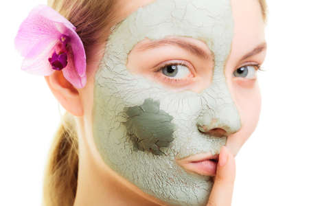 taking care: Skin care. Woman in clay mud mask on face with finger on lips isolated on white. Girl taking care of dry complexion. Secret of beauty. Stock Photo