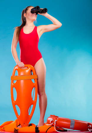 women bathing: Accident prevention and water rescue. Attractive female model in lifeguard outfit on duty looking through binocular keeping float lifesaver equipment on blue