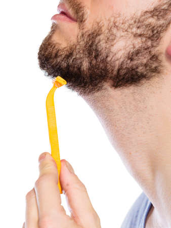 Health beauty and skin care concept. Closeup male face profile. Young man guy styling beard holding disposable yellow razor blade white background. photo