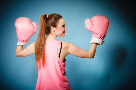 girl punch: Funny girl female boxer model wearing big fun pink gloves playing sports boxing studio shot blue background