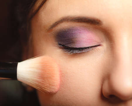 makeover: Cosmetic beauty procedures and makeover concept. Closeup part of woman face makeup detail. Applying rouge blusher with brush
