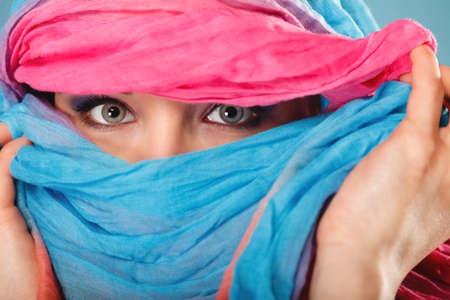 Young woman makeup on eyes hiden her face with multicolored shawl blue background photo