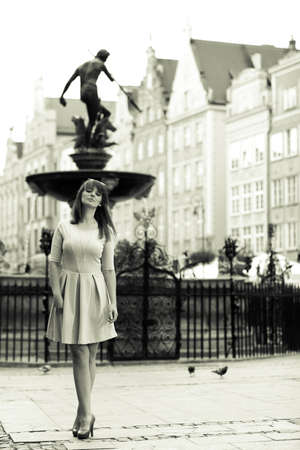 Holidays and tourism concept.  Full length pretty woman in elegant dress outdoor on the street of the old town european city Gdansk Danzig Neptune fountain Poland. Blach white photo photo