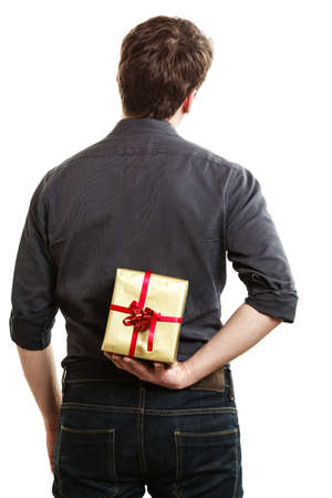 gold gift box: Holiday and special occasion. Man giving golden gift box with red ribbon isolated on white. Guy hiding present behind his back. Surprise. Studio shot.