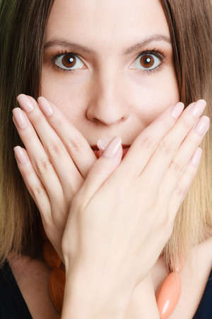 wide eyed: Speak no evil concept. Surprised woman face wide eyed covering her mouth with hands