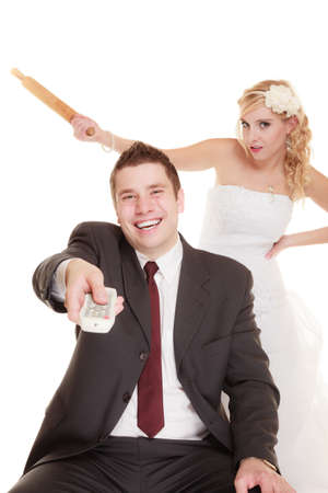 Wedding couple having argument - conflict, bad relationships. Angry woman fury bride holds rolling pin in fight with groom. Isolated