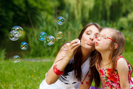 blowing bubbles: Family happiness and carefree concept. Mother and daughter little girl having fun blowing soap bubbles together in park, green blurred background Stock Photo