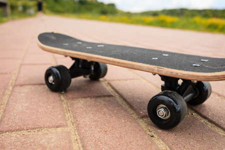 summer sports: Sport equipment. Lone skateboard deck outdoor on paving stone
