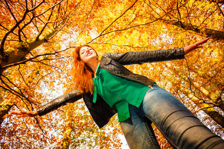 extreme angle: Season and happy people concept. Unusual low angle view of young happy woman in autumn park. Beauty redhaired girl relaxing playing in flying outdoor