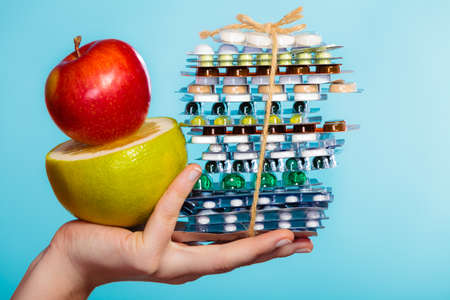healthy choices: Health and balanced diet concept. Choice between two sources of vitamins - pills or fruits. Closeup female hand holding stack of drugs apple and grapefruit on blue.
