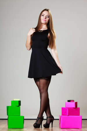Elegant woman in black dress in full length with many pink and green presents gift boxes on gray